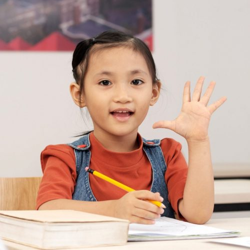 Excited Vietnamese schoolgirl raising arm to answer the question